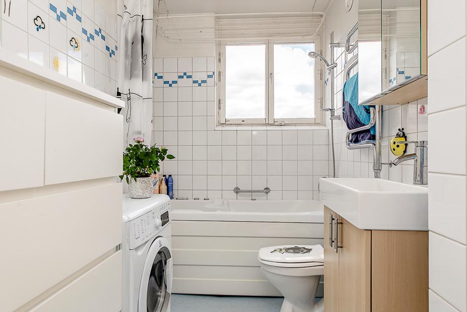 Badrum med tvättmaskin och bubbelbadkar