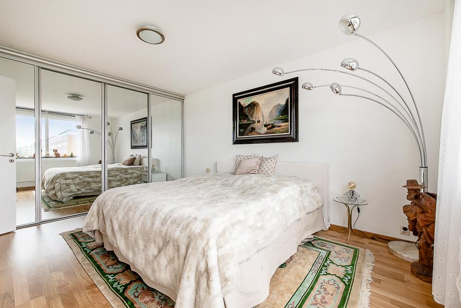 Sovrum med hel garderobsvägg med spegeldörrar