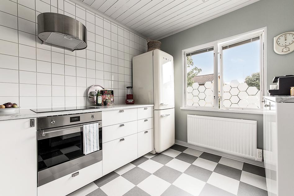 Tidstypiskt kök med helkaklade väggar, marmorskiva mm