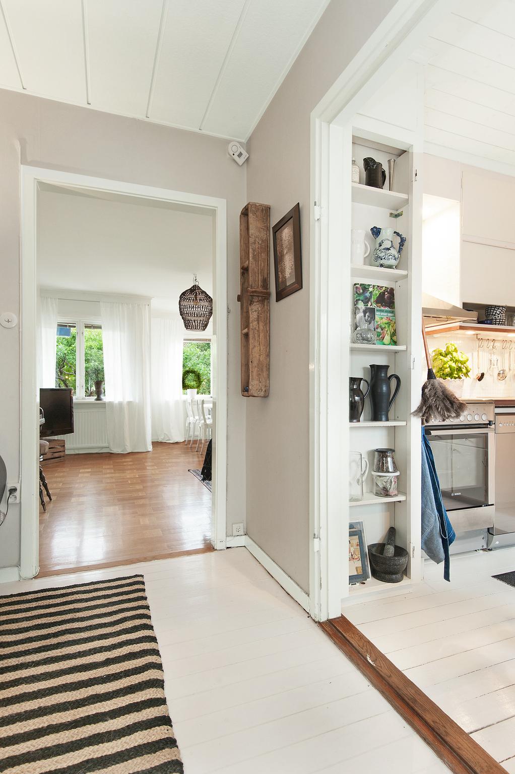 Hall med glimt i kök och vardagsrum