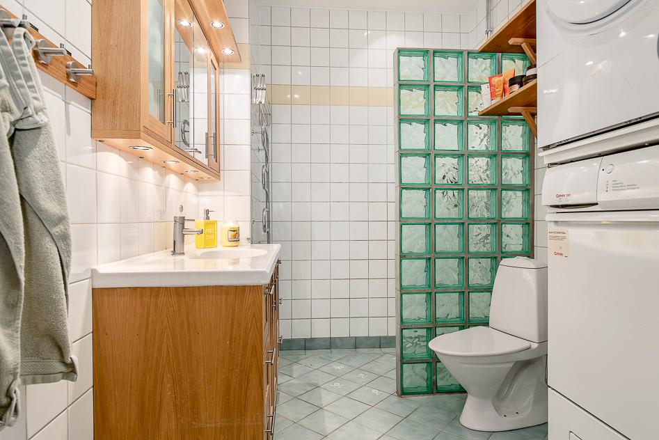 Helkaklat badrum med tvättmaskin och torktumlare