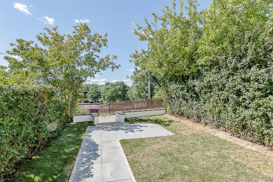 Trädgård med plattsättning och gräs med öppning mot gångväg och lekplats